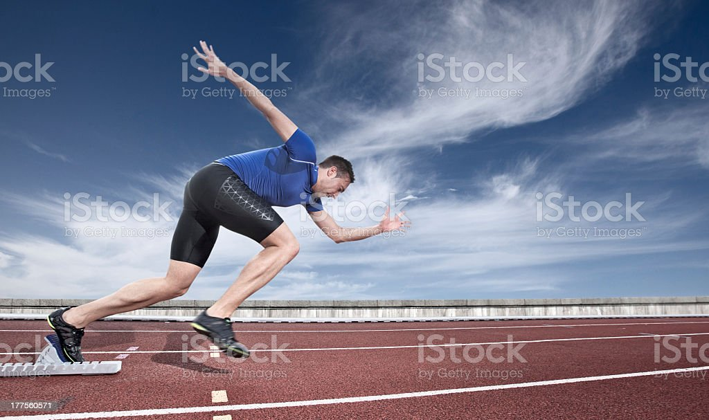 Young athlete launching from a starting block stock photo
