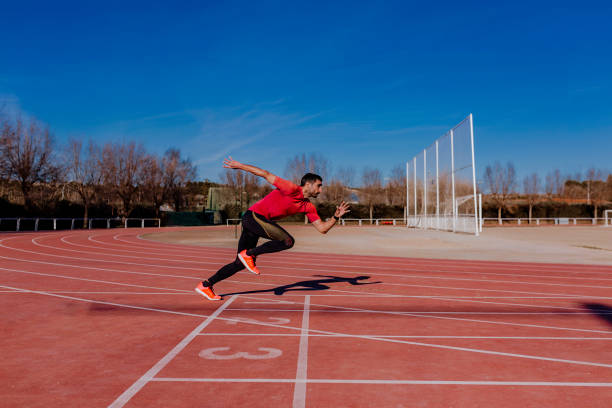 young athlete man running in the lanes. Daylight. Sports concept stock photo