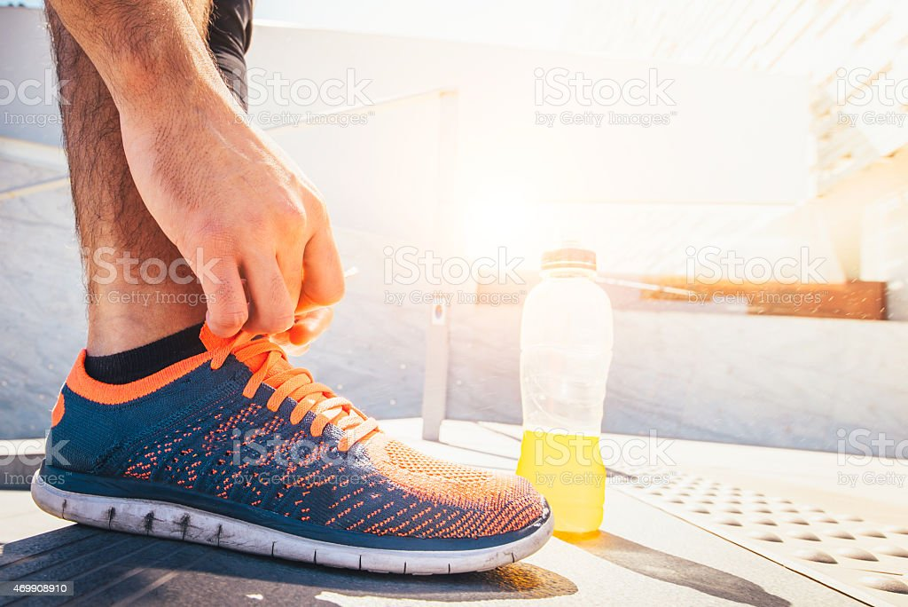 Young Athlete Man Tying Jogging Shoes While Training stock photo