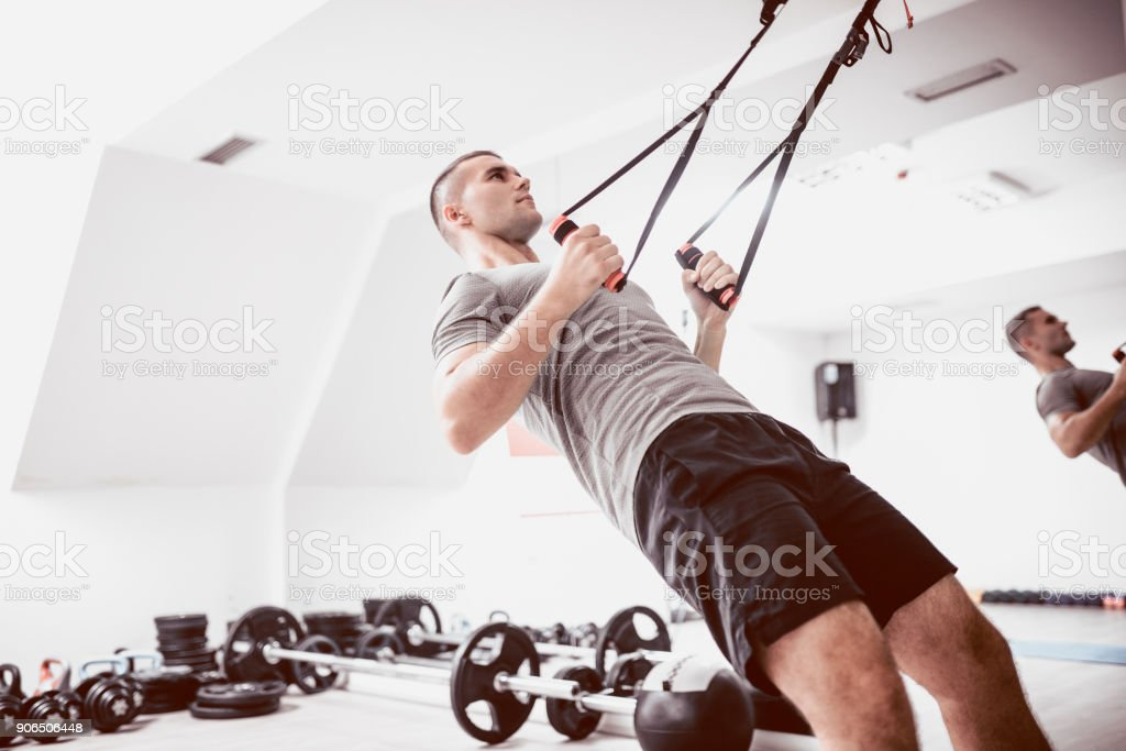 Young Athlete Men Doing Back Exercise With Suspension Straps in Gym stock photo