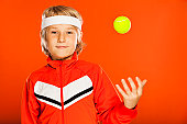 Sporty kid, tossing tennis ball on orange background.