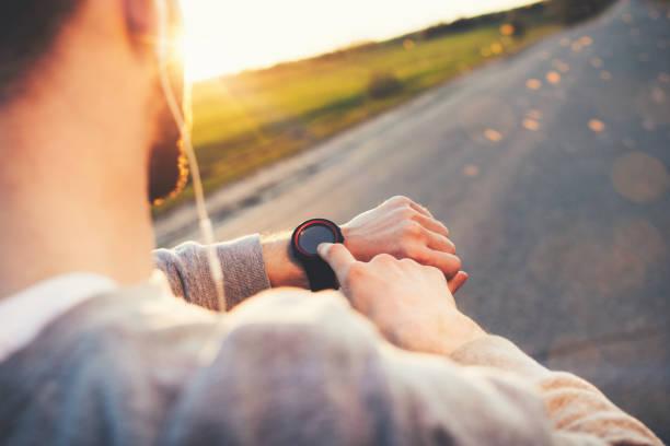 Junge Sportler Läufer im Kopfhörer eine moderne intelligente Uhr schaut und zählt nach oben verbrauchte Kalorien nach Training im Freien bei Sonnenuntergang – Foto