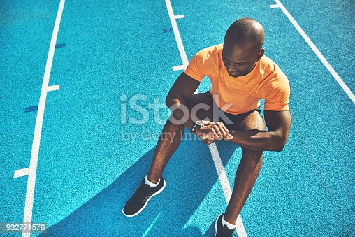 Young African male runner sitting alone on the lanes of a running track checking his lap time on his watch on a sunny day