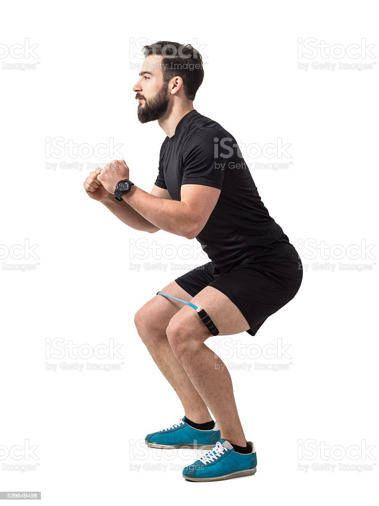 Young athlete squatting exercise with resistance band around legs stock photo