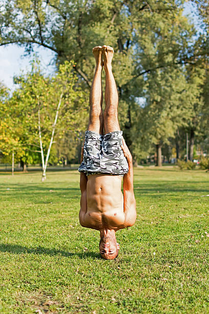Young Athlete Standing on Head in the Park. Street Workout. stock photo