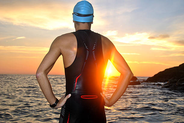 young athlete triathlon in front of a sunrise young athlete triathlon in front of a sunrise over the sea wetsuit stock pictures, royalty-free photos & images