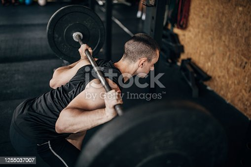 One young male athlete training with weights in the local gym.