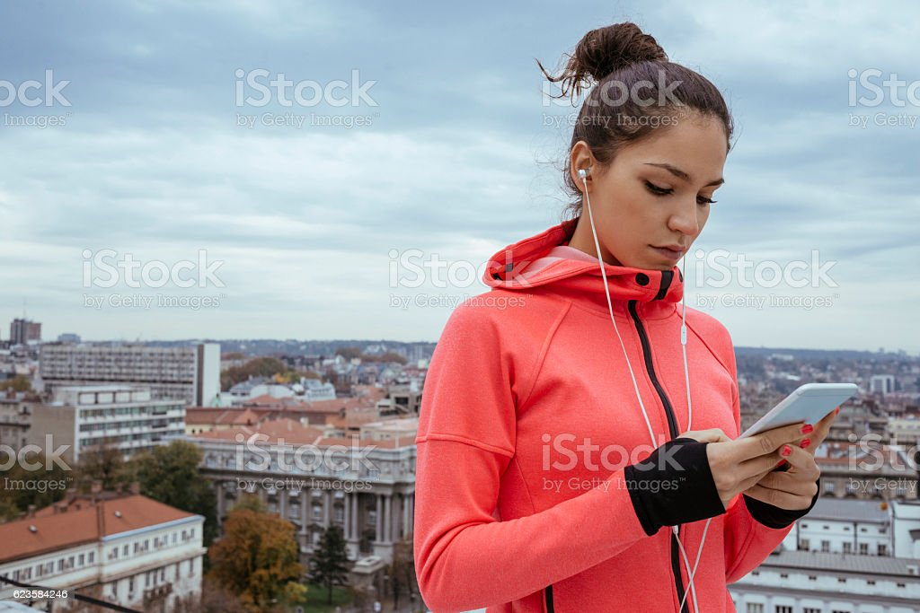 young athlete woman using her smartphone after workout stock photo