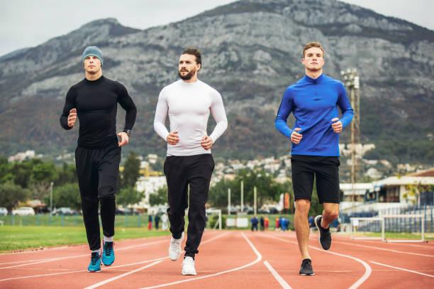junge sportler üben einen run auf stadion für leichtathletik. - sweatpants stock-fotos und bilder