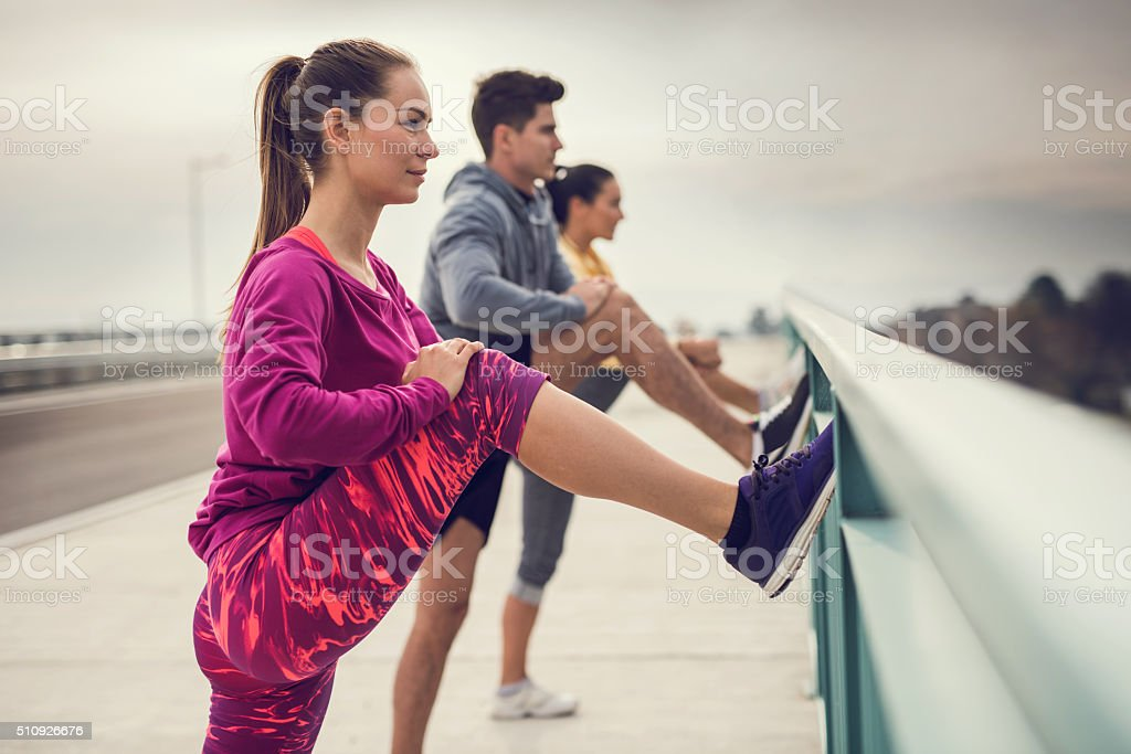 Young athletes stretching their legs outdoors before exercising. stock photo
