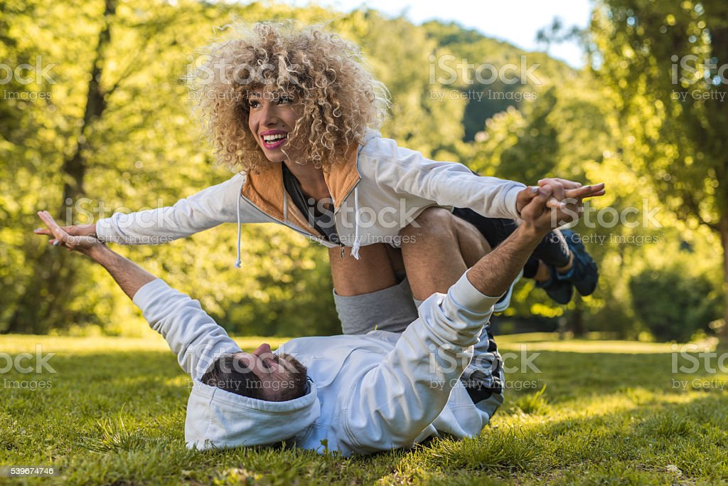 Young athletic couple exercising acro yoga in the park. stock photo