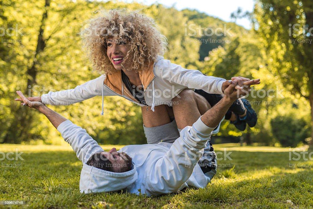 Jeune couple sportif exerçant Acro yoga dans le parc. - Photo
