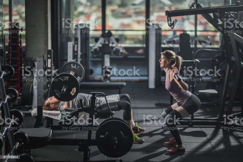 Young athletic couple having body building training in a gym. stock photo