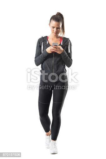istock Young athletic female runner in sportswear using cell phone. 870157506