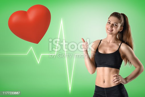 istock Young athletic fitness girl with red heart and heart rhythm cardiogram on green background 1177233887