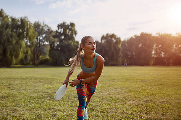 Young athletic girl playing frisbee Young athletic girl playing frisbee in the park. Professional player. Sport concept plastic disc stock pictures, royalty-free photos & images