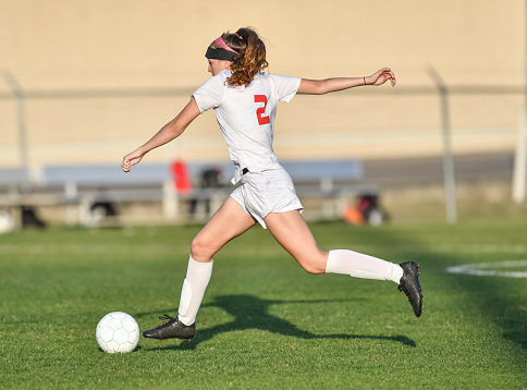 Very athletic young girl kicking and dribbling the soccer ball on a grassy green field.