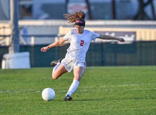 在綠草地裡玩足球的年輕運動女孩 - 女性 個照片及圖片檔