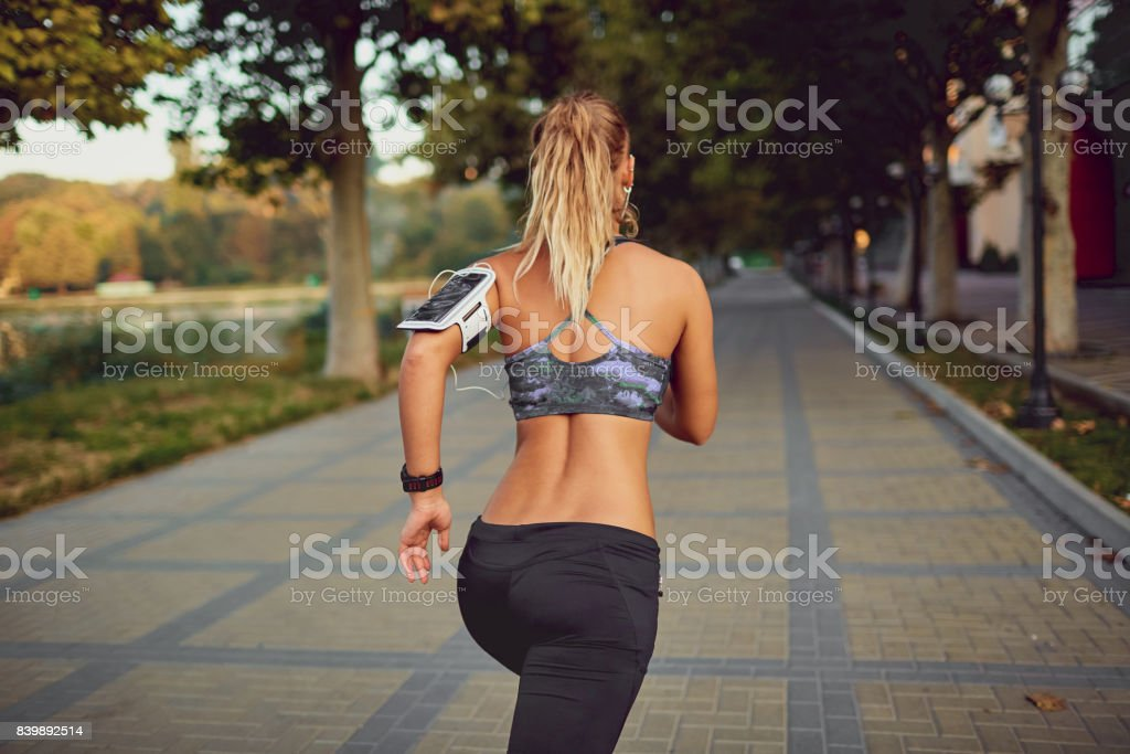 Young athletic girl runner jogging in park in  summer autumn stock photo