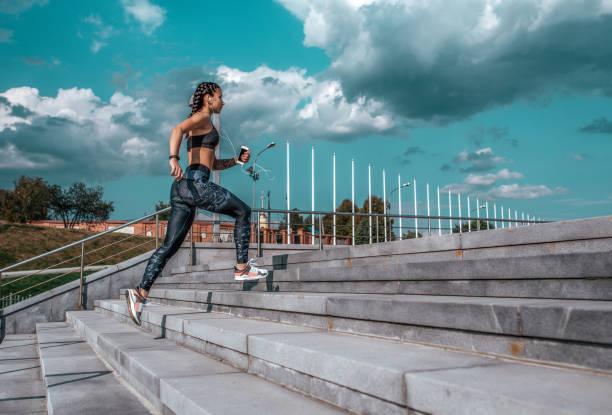 junge sportliche mädchen laufen am morgen für joggen, fitnesstraining, sportbekleidung, leggings und top. telefon hört musik-kopfhörer. sommer-city-workout, online-playlist-anwendung im internet. freiraum. - gymnastik tattoo stock-fotos und bilder
