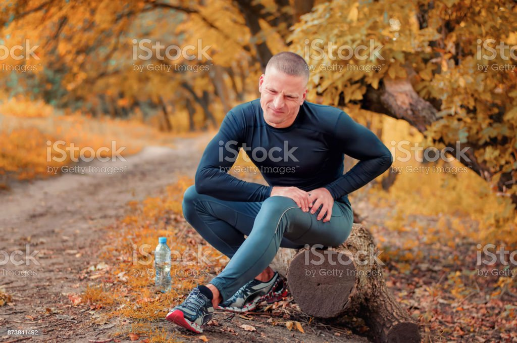 A young athletic  jogger feels a strong pain in the muscle after cramping. stock photo