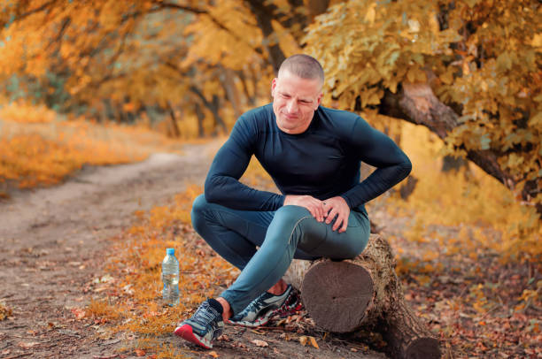 a young athletic  jogger feels a strong pain in the muscle after cramping. - carpet runner stock photos and pictures