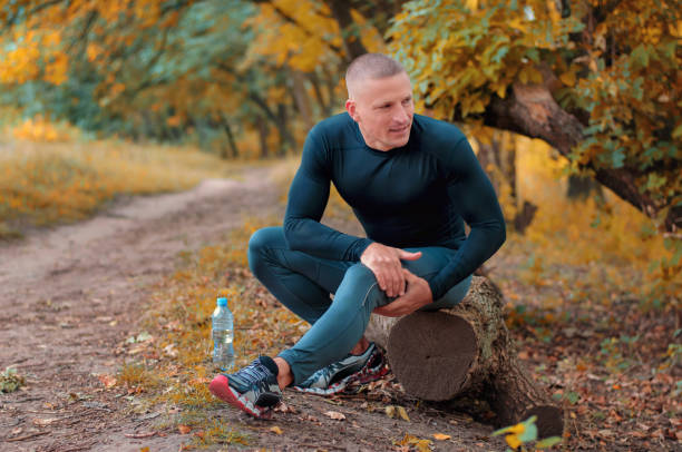 a young athletic  jogger in black tight fitting sportswears holding a hip with his hands after cramping. - carpet runner stock photos and pictures