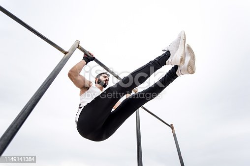 istock Young athletic man doing an ab workout and pull ups. 1149141384