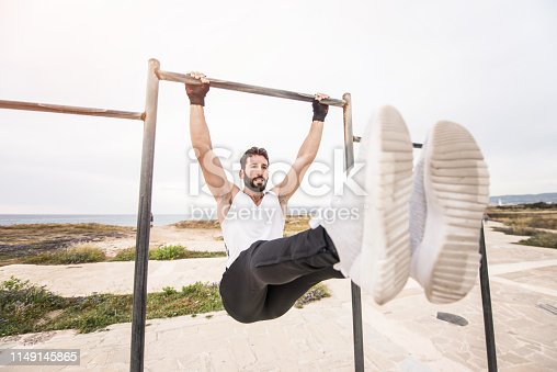 istock Young athletic man doing an ab workout and pull ups. 1149145865