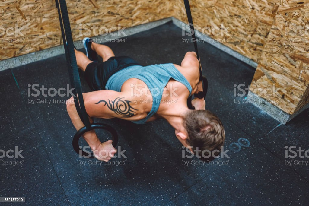 Young athletic man doing pull ups with gymnastic rings stock photo