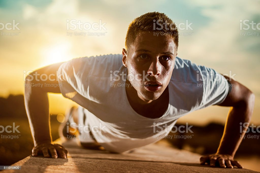 Young male jogger athlete training and doing workout outdoors in...
