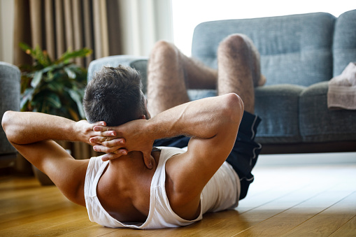 Young athletic man doing sit-ups in the living room