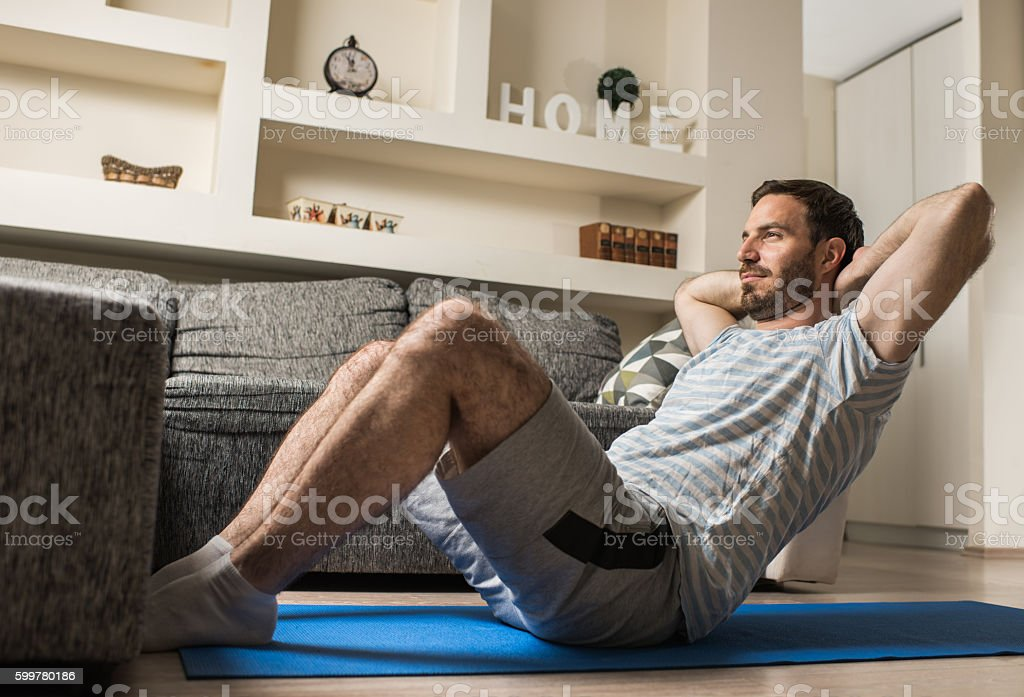 Junger athletischer Mann beim Sit-up im Wohnzimmer. - Lizenzfrei Athlet Stock-Foto