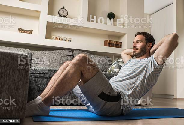 Junger Athletischer Mann Beim Situp Im Wohnzimmer Stockfoto und mehr Bilder von Athlet