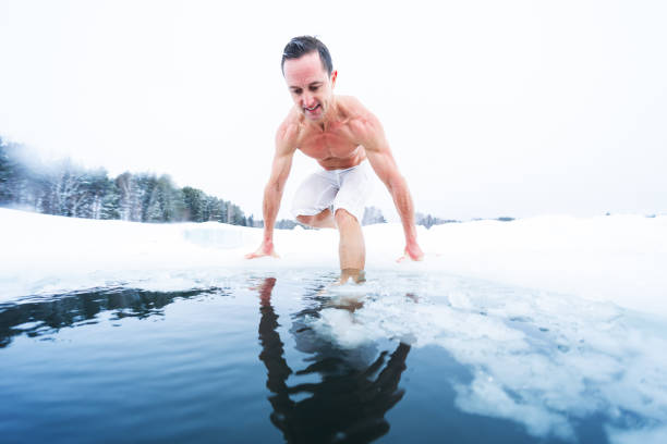 Young athletic man going to have ice bath in the winter pond stock photo