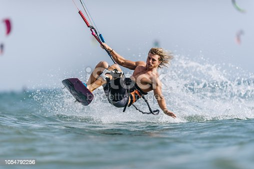 Athletic man kiteboard surfing during summer day at sea. Copy space.