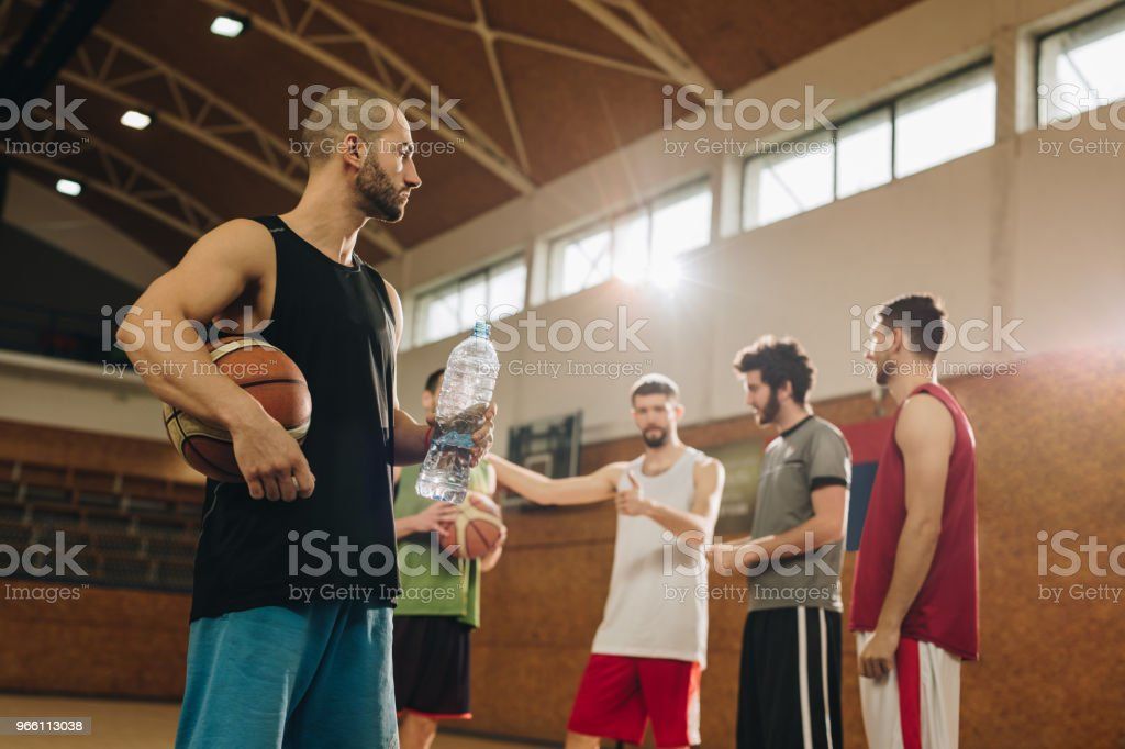 Young athletic man having water break after playing basketball with friends. - Royalty-free Adult Stock Photo