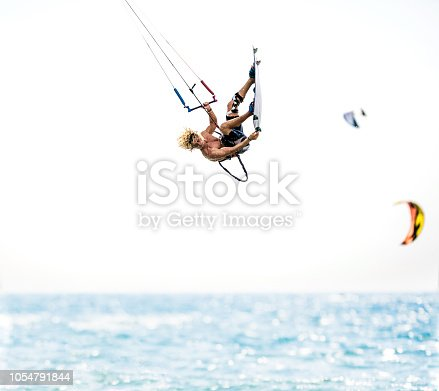 Young man flying with kiteboard above the sea. Copy space.