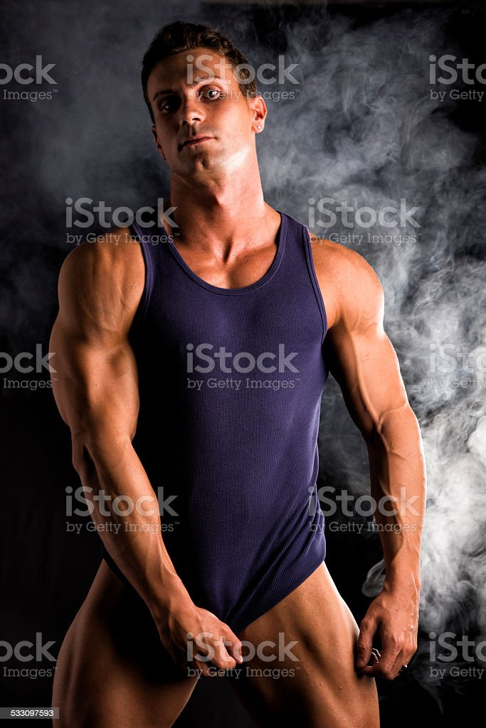 Young athletic man pulling down tanktop on ripped muscular torso stock photo