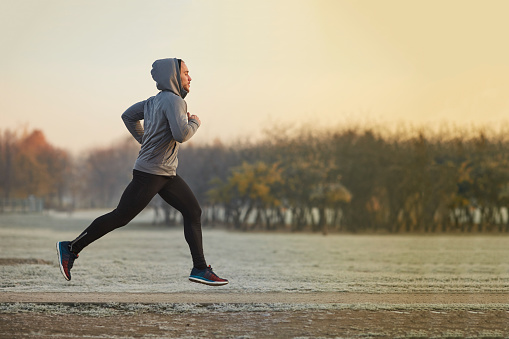 Young athletic man running at park during cold autumn morning