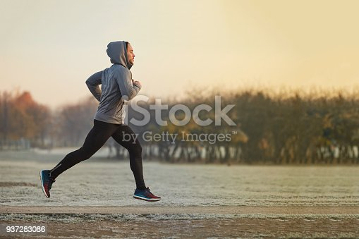 istock Young athletic man running at park during cold autumn morning 937283086