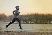 寒い秋の朝の間に公園でランニングする運動青年