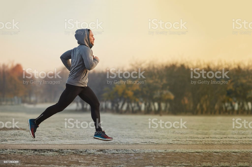 Young athletic man running at park during cold autumn morning stock photo