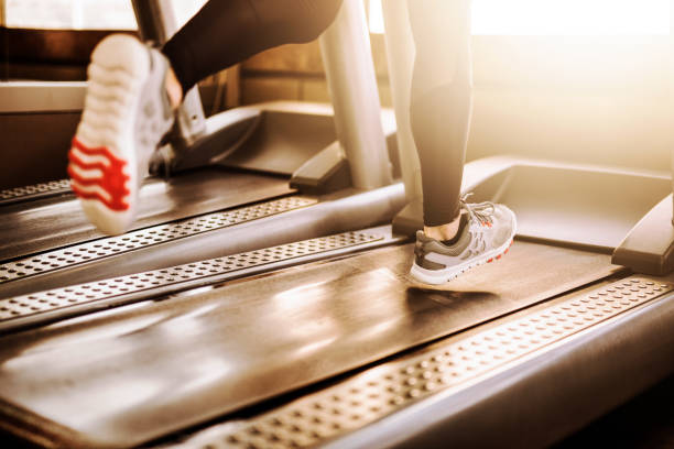 Young athletic man running on treadmill legs close up stock photo