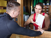 Young athletic man talking to girl at reception while taking for rent surf equipment in surf club