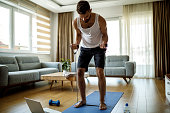 istock Young athletic man training with stretching band at home 1276686232