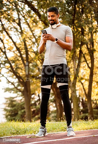 istock Young athletic man using a mobile phone while standing on a running track in a public park 1144866592