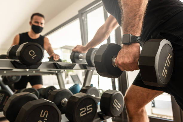 Young athletic man wearing a prevention face mask during his workout in the gym stock photo