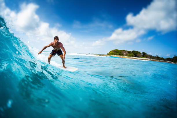 Young athletic surfer rides the ocean wave on Sultans surf spot in Maldives. Tilt shift effect applied stock photo