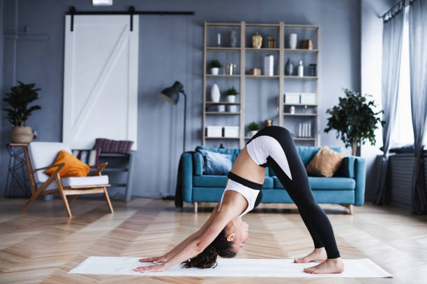 Young athletic woman doing exercises in the living room. stock photo